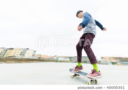 The teenager skateboarder rides the skatepark in cloudy weather. Youth Urban Culture. 40000301
