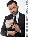 man in black suit holds pomeranian dog 40000865