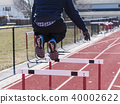 Athlete jumping over hurdles on a track 40002622