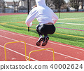 Athlete in white hoody jumps over yellow hurdles 40002624