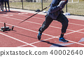 Athlete pulling a sled with weights on a track 40002640