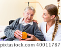 Nurse giving physical therapy to senior woman 40011787