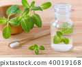 alternative natural mouthwash bottle with mint and wood toothbrush closeup on wooden 40019168