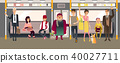 People in subway inside train sitting, standing and holding on to handrails while riding in 40027711