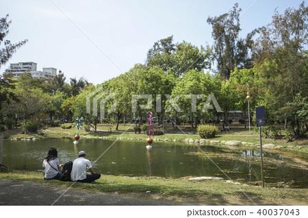 一對情侶坐在公園湖邊的草地上聊天 40037043