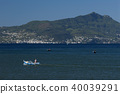 Fisherman on boat, ischia island in the background 40039291