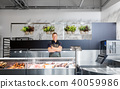 male seller with seafood at fish shop fridge 40059986
