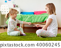 girls playing rock-paper-scissors game at home 40060245