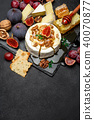 Camembert cheese and walnuts on stone serving board 40070877