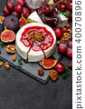 Camembert cheese and walnuts on stone serving board 40070896