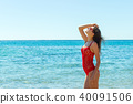 woman on tropical beach in swimsuit and glassses 40091506