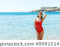 woman on tropical beach in swimsuit and glassses 40091514