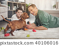 Cheerful family and dachshund dog playing with ball 40106016