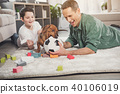 Happy parent and boy having fun with puppy 40106019