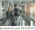 Beaming lady telling with glad man with suitcase 40119345