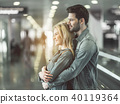 Beaming man embracing outgoing female 40119364