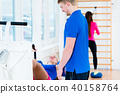 Men and women doing workout on diverse equipment in gym 40158764