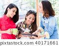 Three young women having fun while looking at a tablet PC during break 40171661