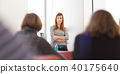 Woman giving presentation in lecture hall at university. 40175640
