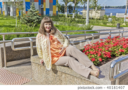 Pregnant woman in orange sitting on embankment 40181407