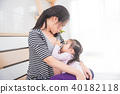 woman breast feeding her daughter at home 40182118