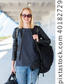 Portrait of young cheerful female traveler wearing casual clothes carrying heavy backpack and 40182729