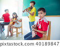 boy playing ukulele with friend in music classroom 40189847