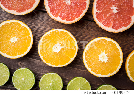Colorful citrus halves on wooden table. 40199576