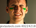 Portrait of a man with the flag of the Brazil painted on him face. 40224218