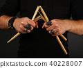 Man hands with broken drumsticks over black 40228007