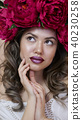 Girl model posing. a young woman in a wreath of scarlet peonies on her head, dark long curly hair 40230258