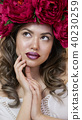Girl model posing. a young woman in a wreath of scarlet peonies on her head, dark long curly hair 40230259