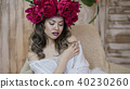 Girl model posing. a young woman in a wreath of scarlet peonies on her head, dark long curly hair 40230260