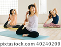 採取瑜伽教訓的年輕日本婦女在瑜伽演播室 40240209