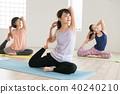 採取瑜伽教訓的年輕日本婦女在瑜伽演播室 40240210