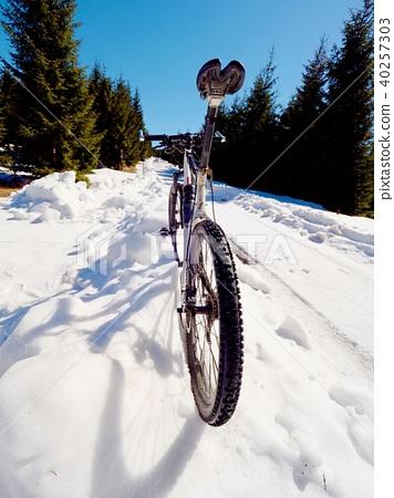 Mountain bike in frozen snow against blue sky.  40257303