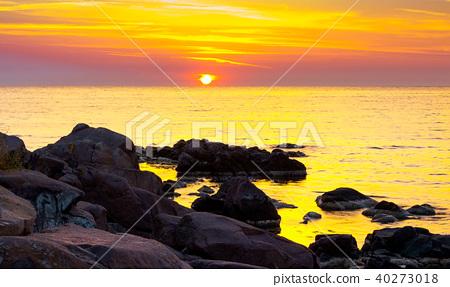 reddish sunrise over the sea with rocky shore 40273018