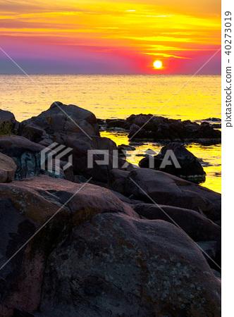 reddish sunrise over the sea with rocky shore 40273019