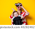 little baby in carrier and mother with binoculars 40282462