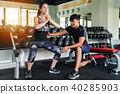 Woman doing squat with a personal trainer 40285903