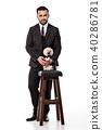 man in black suit holds pomeranian dog 40286781