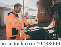 Garbage man and women cleaning dustbins into waste truck 40288000