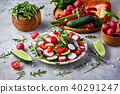 Creative fresh vegetable salad with ruccola, cucumber, tomatoes and raddish on white plate 40291247