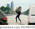 Man trying to carry a glass jar full of dollars 40296048