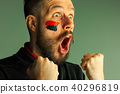 Portrait of a man with the flag of the Germany painted on him face. 40296819