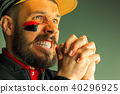 Portrait of a man with the flag of the Germany painted on him face. 40296925