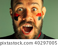 Portrait of a man with the flag of the Germany painted on him face. 40297005