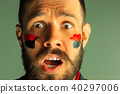 Portrait of a man with the flag of the Germany painted on him face. 40297006