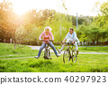 Beautiful senior couple with bicycles outside in spring nature. 40297923