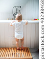 A toddler child standing at the bath in the bathroom at home. 40298468